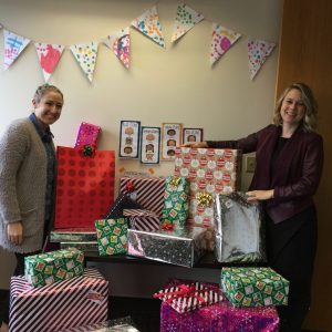 Lauren and Jenny with a stack of wrapped holiday gifts for Michelle's Love family.