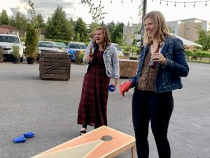 Christina and Sarah playing cornhole at end-of-year party at Rossi Farms.