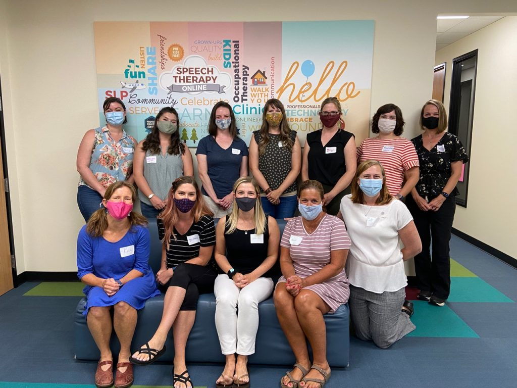 12 women wearing masks standing and sitting in front of the hello clinic mural