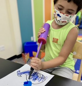 Boy making a whale craft with paper, markers and paint for the water spout.