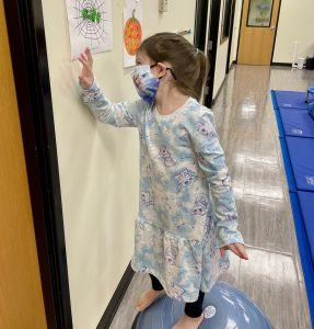 Child on balance ball with a picture of a spider web with green play-doh spider family at The Hello Clinic gym..